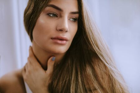 Photo pour Pretty young long hair female brunette in front of the window - image libre de droit