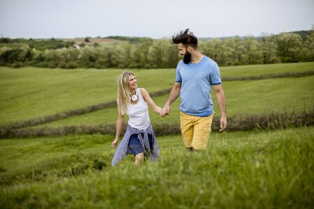 Photo for Loving young couple enjoying a walk through grass land on a summer day - Royalty Free Image