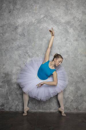 Photo pour Pretty young ballerina dancer dancing classical ballet against rustic wall - image libre de droit