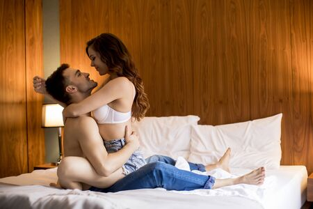 Foto de Sexy woman in bra sit on handsome guy and embrace him with legs on a bed at the bedroom - Imagen libre de derechos