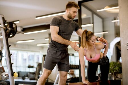 Photo pour Attractive woman and a personal trainer with dumbbell weight training at the gym - image libre de droit