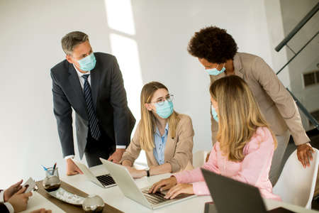 Photo pour Group business people have a meeting and working in the office and wear masks as protection from corona virus - image libre de droit