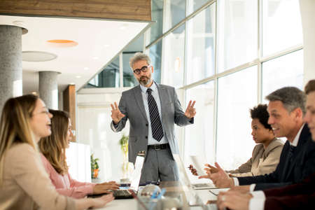 Photo pour Mature businessman explaining strategy to group of multiethnic business people while working on new project in the office - image libre de droit