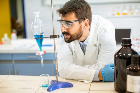 Foto de Researcher working with blue liquid at separatory funnel in the laboratory - Imagen libre de derechos
