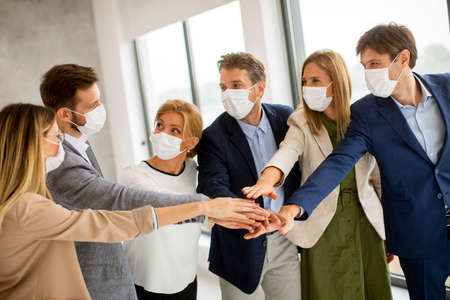 Photo pour Group of business people with protective facial masks holding hands together in the office - image libre de droit