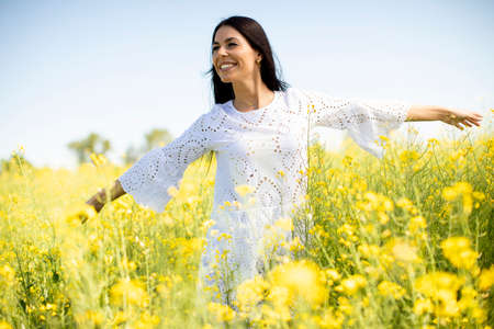 Photo pour Pretty young woman in the rapeseed field - image libre de droit