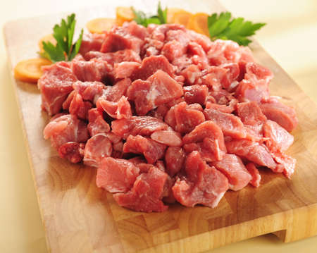 raw beef stew on a wooden cutting board.