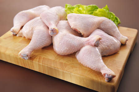 Fresh raw chicken legs arrangement on kitchen cutting board