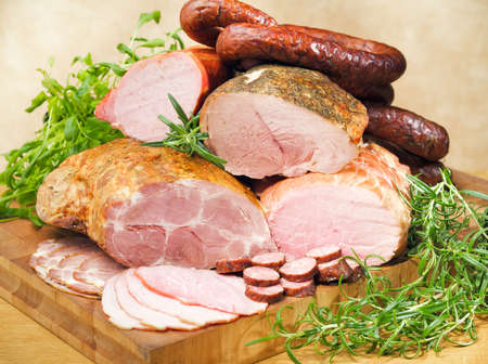 Photo pour Sausages and meats on a cutting board and table - image libre de droit