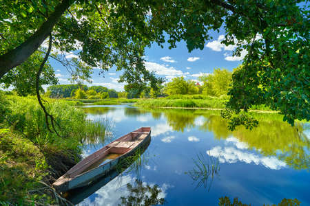 Spring summer landscape blue sky clouds Narew river boat green trees countryside grass Poland water leavesの写真素材