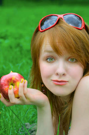 nice girl with apple on grass