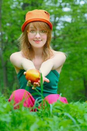 girl in bonnet with apple outdoor