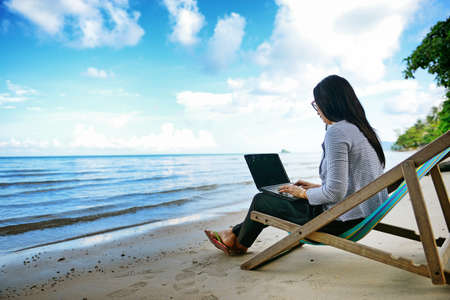 Photo for Business woman using a laptop beside the beach - Royalty Free Image