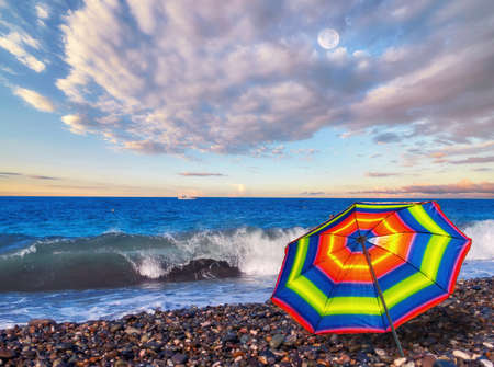 Photo pour Panoramic view of rainbow umbrella on summer beach of tropical sea with azure waves and white ship under dramatic cloudy sky - image libre de droit