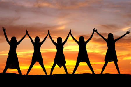 Happy celebrating women at sunset or sunrise standing elated with arms raised up above their heads