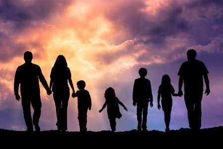 Silhouette of a family comprising a father, mother and children walking into the sunset