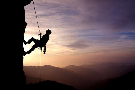 Foto de Silhouette of a climber on a vertical wall over beautiful sunset - Imagen libre de derechos