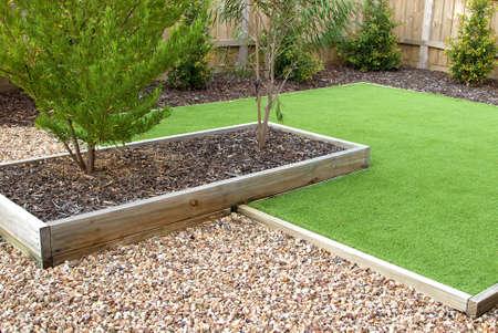 Photo pour Combination of timber, plants, artificial grass, decorative gravel and mulch - image libre de droit