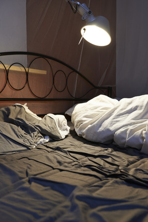 Photo pour Disheveled sheets and pillows year of unmade bed, led light and Mosquito Netting - image libre de droit