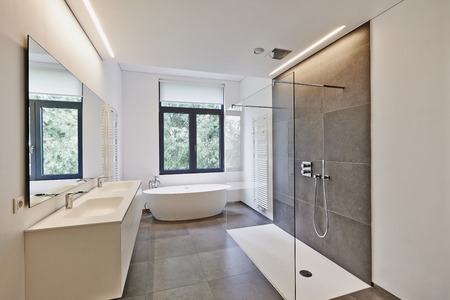 Photo for Bathtub in corian, Faucet and shower in tiled bathroom with windows towards garden - Royalty Free Image