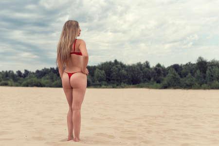 Foto de Walking along the beach with a woman in a swimsuit - Imagen libre de derechos