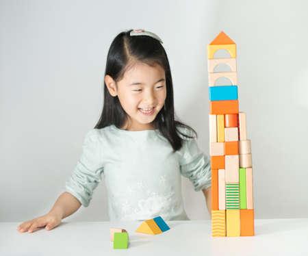 Photo pour little Asian girl playing colorful wood blocks - image libre de droit