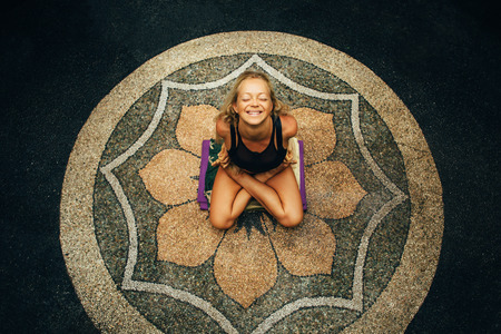 Blonde woman with sunburnt slim body makes yoga exercises outside in the center of flower pattern and laugh. Yoga pose