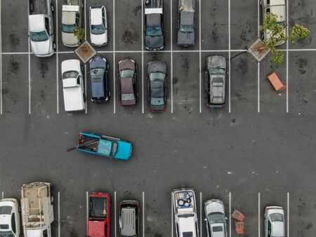 Photo for Aerial top view of parking lot at supermarket with with varieties of colored vehicles. People walking to their car and trying to park. - Royalty Free Image