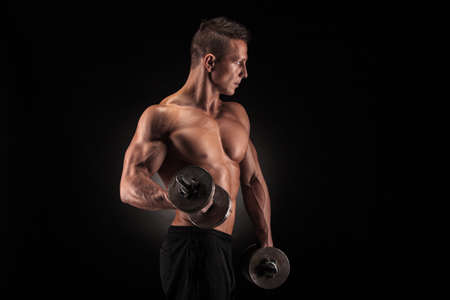 Handsome power athletic man bodybuilder doing exercises with dumbbell. Fitness muscular body on dark background.
