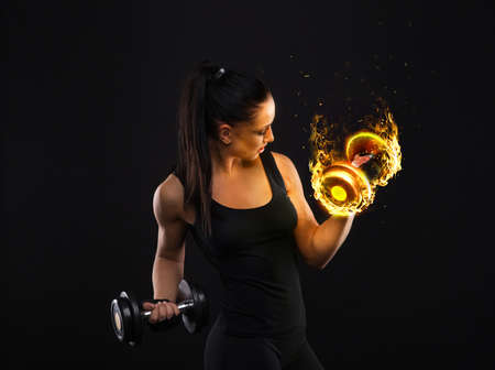 Photo pour Young sportslooking nice lady with dark hair shows various performs exercises with equipment on the black background in studio - image libre de droit