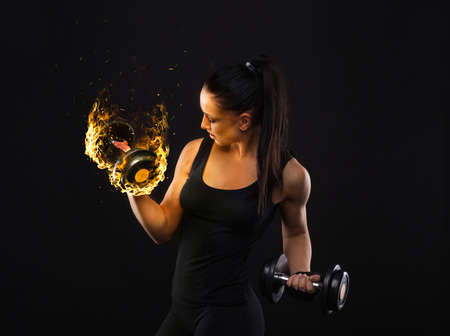 Young sportslooking nice lady with dark hair shows various performs exercises with equipment on the black background in studio