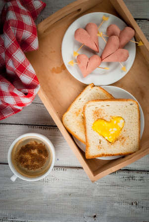 Idea for the celebration of Valentine's day: breakfast - toast with scrambled eggs in the form of hearts, sausages and cheese in the form of hearts and aromatic coffee with cinnamon, copy space top view