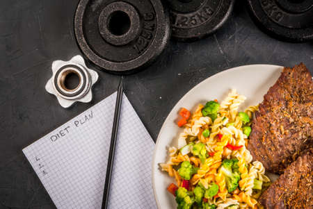 Concept of dieting, counting calories: a plate of healthy food (whole grain pasta with vegetables); dumbbells and weights on them, notes for doing a food diary