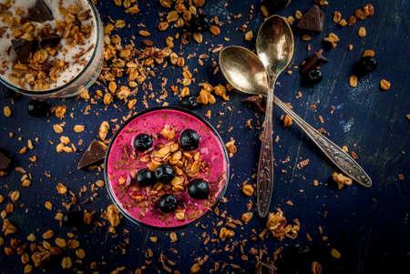 Easy and light healthy dessert of yogurt, fruit smoothies, granola and dark chocolate on a dark blue table, sprinkle dessert ingredients