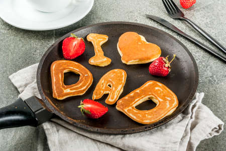 Celebrating Father's Day. Breakfast. The idea for a hearty and delicious breakfast: pancakes in form of congratulations - I love dad. In a frying pan, coffee mug and strawberries. copy space