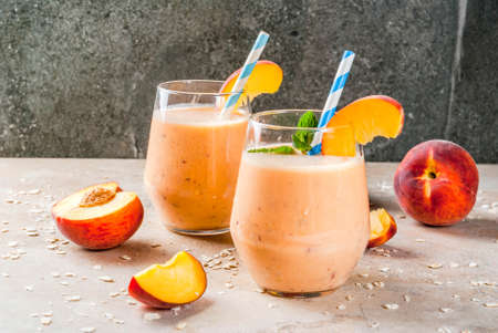 Healthy eating. Breakfast, snack. Drink smoothies from fresh peach, milk (yogurt) and oatmeal, decorated with mint leaves, with striped straws.