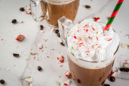 Homemade Peppermint Mocha, Christmas coffee drink with candy canes, whipped cream and mint syrup , on white marble table, copy space