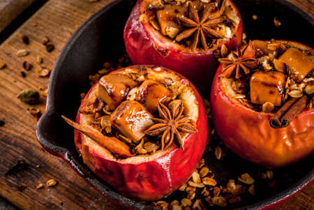 Photo pour Autumn food recipes. Baked apples stuffed with granola, toffee and spices. On black stone table, in frying pan, copy space - image libre de droit