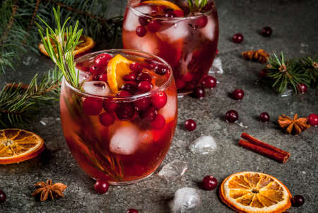 Foto de Christmas winter drinks. Cold cocktail with cranberries, orange, rosemary, with spices (cinnamon, anise) and ice, on a dark stone table, Copy space - Imagen libre de derechos