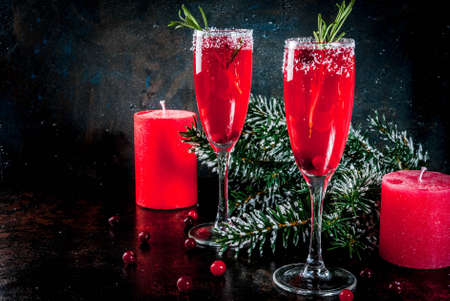 Christmas morning red cranberry mimosa with rosemary, dark background copy space with christmas decorations