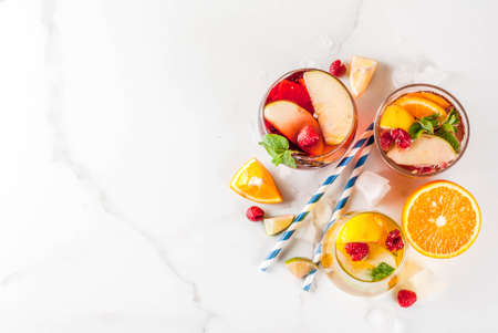 Summer cold cocktail, set of three fruit and berry sangria drink. red white pink, with apple, lemon, oranges and raspberry. light background, copy space  top view