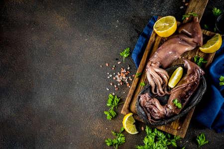 Foto de Fresh raw seafood, squid with lemon and light for preparation on a light blue background - Imagen libre de derechos