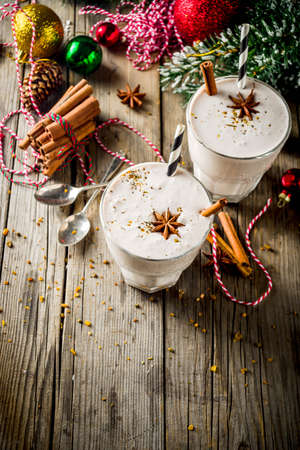 Photo pour Christmas sweet cold drink, Homemade eggnog milkshake in two glasses with cinnamon and anise, old wooden background with xmas decorations copy space - image libre de droit