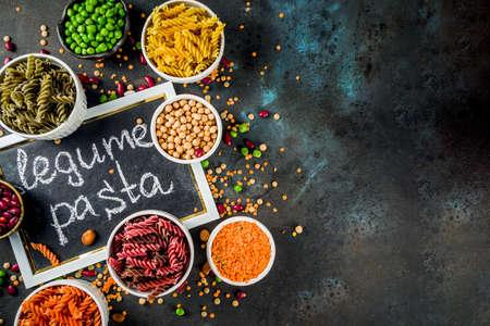 Photo pour Trend healthy food, vegan diet concept. Multi colored legume pasta with raw beans. Beans, chickpeas, green peas, lentils. Copy space top view - image libre de droit