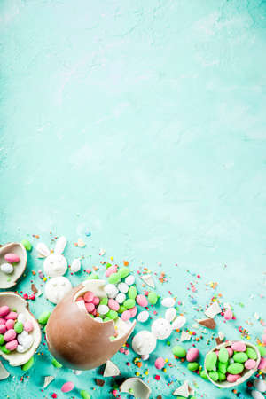 Photo for Colorful spring easter sweets background, with chocolate eggs, sugar sprinkles and marshmallow bunny, turquoise light blue concrete background copy space top view - Royalty Free Image
