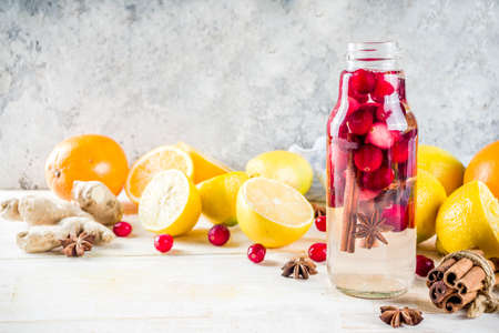 Photo pour Set of various fall and winter refreshing infused water, sweet sour healthy beverages with oranges, honey, cranberry, mint, rosemary, cinnamon and spices, white wooden background copy space - image libre de droit