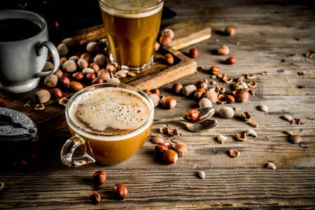 Photo pour Homemade hazelnut coffee latte or cappuccino, rustic wooden background with hazelnuts, three coffee cups copy space - image libre de droit