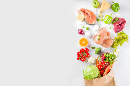 Foto de Healthy food shopping concept, Balanced diet ingredient - meat, fish, fruit, vegetables. Fresh foods with paper shopping bag, top view on white background copy space - Imagen libre de derechos