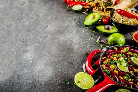 Foto de Cinco de Mayo food.Mexican food concept background with taco, quesadilla, burrito, chili, salsa sauce, hot pepper, lime. Black concrete background top view copy space - Imagen libre de derechos