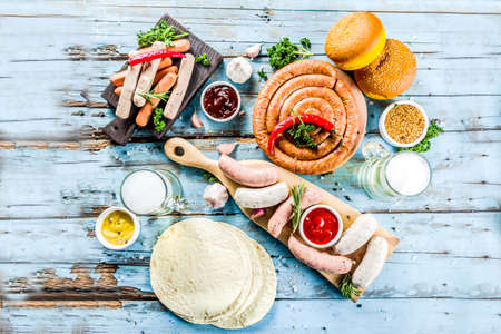 Photo pour Different bbq picnic party food with beer  various grilled sausages, burger buns, flat taco bread, beer, old wooden background copy space - image libre de droit